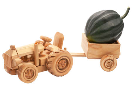 Green pumpkin in wooden toy tractor cart, isolated on white background. photo