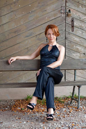 Beauty, mature woman sitting lean on old wooden board wall. photo