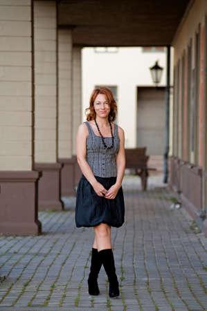 Mature, beautiful woman posing on the pavement street near arc. photo