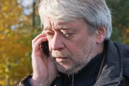 Mature busy man with grey hair in forest talking on the phone in autumn day. photo