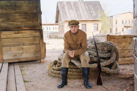 第一次世界大戦の制服を着て銃を持つ兵士、ロープに腰を下ろす。コスチューム アコード世界大戦 I. 写真の時代シネマシティ ラトビアの Cinevilla で 写真素材