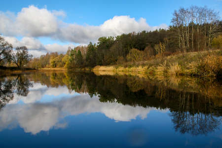 View on autumn landscape of river and trees in sunny day. Forest on river coast in autumn day. Reflection of autumn trees in water. Autumn in Latvia. Autumn landscape with colorful trees and river. 写真素材 - 114958249