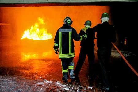 Feuerwehrausbildung zur Brandbekämpfung in Deutschland. Feuerwehrmann im Brandschutzanzug sprüht Wasser, um mit Rauch zu feuern. Feuerwehrmann bekämpft Feuerangriff, während der Trainingsübung