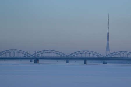 Railway bridge and television tower in winter. Railway bridge over the frozen river Daugava in Riga.TV tower and railway bridge on blue sky background in winter. Riga view in winter.