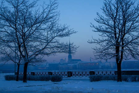 Riga view in winter; Riga, capital city of Latvia in winter time. View of St Peters Church in winter. View of Old Riga with frozen river Daugava in the foreground. City Riga with background of blue sky.