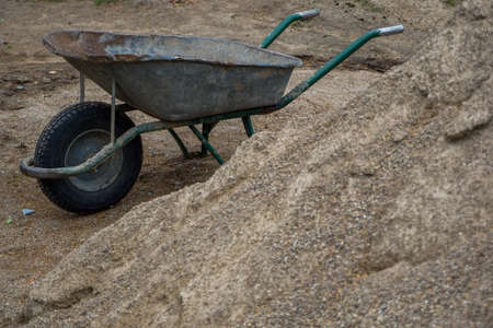 Construction wheelbarrow in the sand by the river Daugava. Wheelbarrow at the gravel pile, Latvia. Wheelbarrow for construction in site building area.