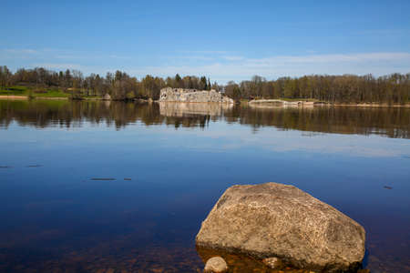 Natural big river Daugava landscape with natural big stones and ruins in Latvia. Koknese castle ruins. Latvian medieval castles. Archaeological monument of national importance.