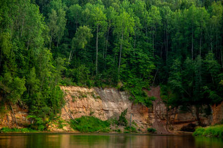 Landscape with cliff, flowing river and green forest in Latvia. Gauja is the longest river in Latvia, which is located only in the territory of Latvia.