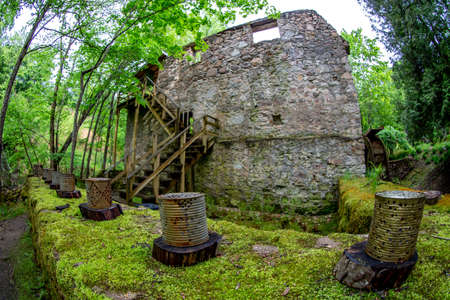 Old water mill and rusted barrels in the beautiful forest park in Latvia. Moss covered ancient mill in old park. Shot with fisheye lens. Stock Photo