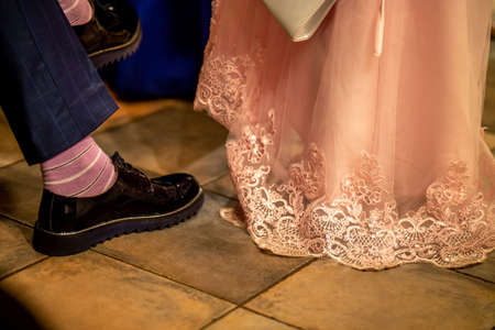 Legs of newlyweds in shoes. Groom in brown wedding shoes and bride in pink wedding dress at the home.