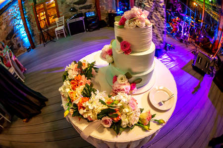 Wedding cake decorated with flowers on table. Three tiered wedding cake and plate with fork on white table. Shot with fisheye lens.