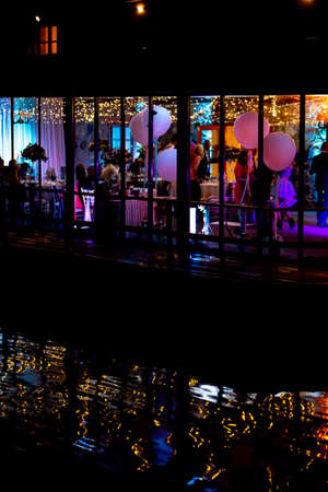 Silhouettes of people in the window during wedding celebrations at night, in the light of colorful spotlights.