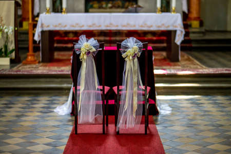 Beautiful floral wedding decoration in a church. Christian church decoration for wedding marriage ceremony. Wedding decor for chairs from flowers, veils and ribbons in church.