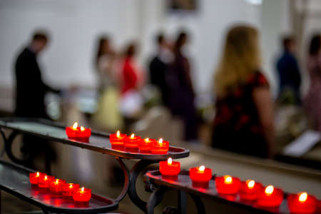 Wedding marriage ceremony in church. Burning candles in the church during the wedding ceremony. Christian church decorated from candles for wedding marriage ceremony.