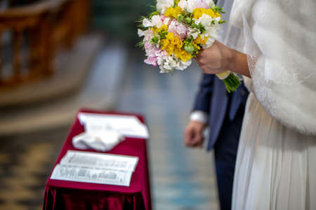 The bride holds a wedding bouquet of beautiful flowers in her hand. The bouquet consists of white, yellow and pink flowers. Marriage registration certificate and grom's hand is In the blur area. Bouquet of flowers in the hand of the bride during the marriage ceremony.