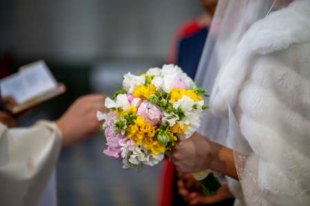 The bride holds a wedding bouquet of beautiful flowers in her hand. The bouquet consists of white, yellow and pink flowers. Priest and brides hands is In the blur area. Bouquet of flowers in the hand  写真素材