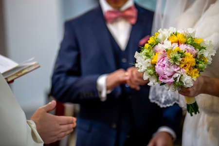 The bride holds a wedding bouquet of beautiful flowers in her hand. The bouquet consists of white, yellow and pink flowers. Priest hand and groom is In the blur area. Bouquet of flowers in the hand of