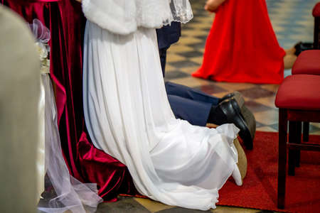 Bride and groom preparing for communion on knees at wedding ceremony in church. Bride and groom during wedding ceremony in church.