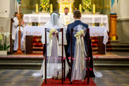 Bride and groom during wedding ceremony in church. Bride and groom preparing for communion on knees at wedding ceremony in church. Chairs decorated with bouquets of flowers and ribbons in church for wedding ceremony.