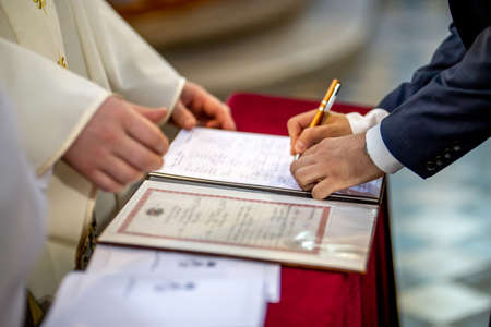 The groom signs documents on registration of marriage in the presence of the pastor. Young couple signs wedding documents in the church during wedding ceremony, Latvia