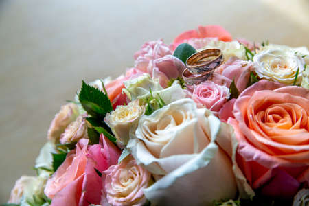 Wedding rings on the bouquet of roses. Wedding rings on bridal bouquet with colorful roses. Bouquet of bride with flowers and gold rings.