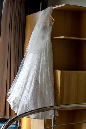 White wedding dress hanging at wooden closet. White bridal dress on the rack at the wardrobe. Wedding clothes for the bride.