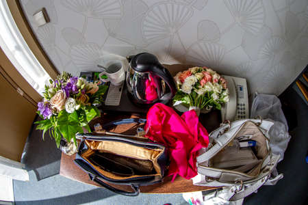 Things from open lady bag. Teapot, phone, coffee mug, red scarf, bags, bouquets of flowers and other cosmetics and womens accessories on bridal table. Things from open lady bag. 写真素材