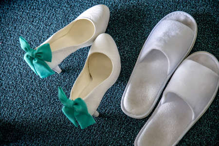 White bridal shoes and wedding slippers on carpet. Wedding shoes with ribbons and white slippers. 写真素材