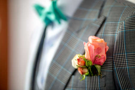 Wedding boutonniere of rose in pocket of checkered jacket of groom. Boutonniere of pink roses in the grooms pocket of jacket. 写真素材
