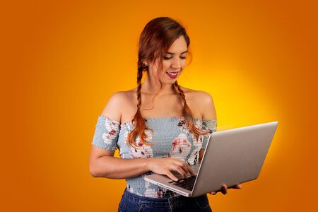 Smiling woman using computer. Yellow background Banco de Imagens