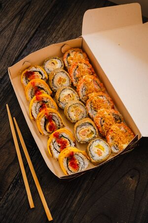 Large amount of sushi served in the container. Ready to eat.
