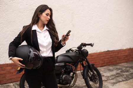 woman using the cell phone before getting on her motorcycle. holding a helmet Banco de Imagens