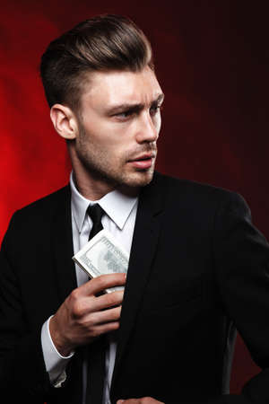 brunette handsome man in a suit on a dark background with money Stock Photo