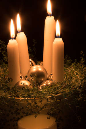 Christmas advent wreath with burning candles laid on table with black background Stock Photo