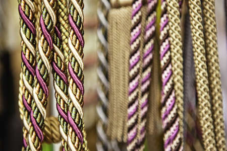 next to each other: Close-up of multicolored ropes, they hang close next to each other in a row