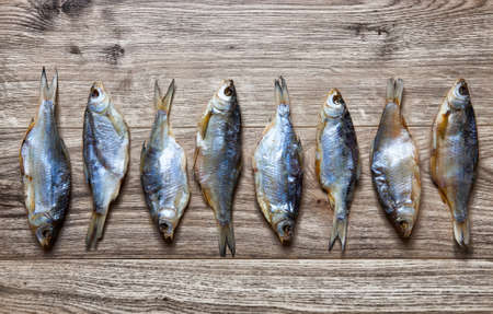 fish rearing: Dry fish on a wooden background  large amount