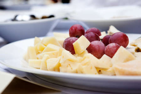 cheese platter: cheese platter with grapes  light background. Selective focus