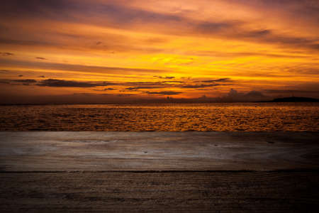 extending: Wooden deck extending into the sea on sunset