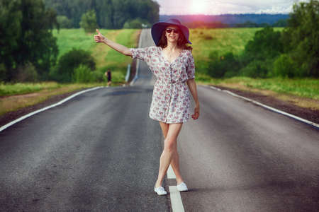 hitchhiking: young girl travels on the highway hitchhiking