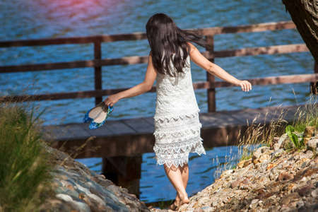 Girl in a white dress going down to the river Stock Photo