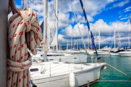 fixed line: Thick ship vessel rigging rope on a boat, marina in background Stock Photo