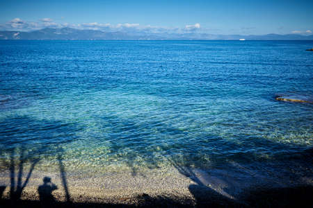 ionio: Ionian sea. shadow of man and trees on water Stock Photo