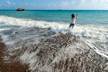 Young woman with long hair play waves running, feeling the sea