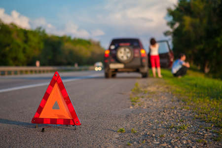 alternateur: Close-up Of A Triangular Warning Sign With Couple Standing In Front Of Broken Down Car