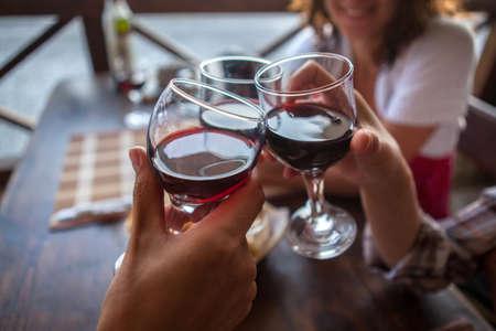 Gelukkige vrienden in een bar drinken rode wijn.
