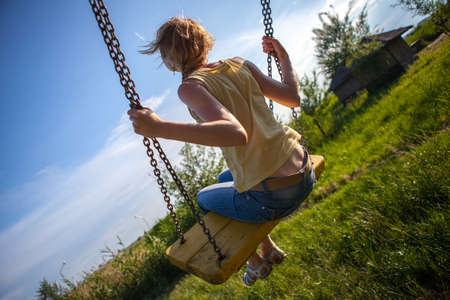 mountainscape: girl swinging on a swing in the village.