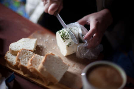 People cut cheese with a knife on old wooden table Stock Photo