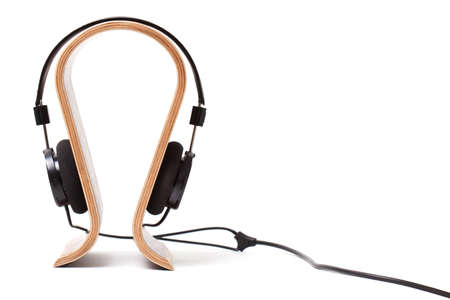 earpiece: Black Pair of Headphones on a wooden stand Isolated on a White Background Stock Photo