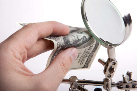 one hundred dollars: Finance inspector. Checks money for authenticity through a magnifying glass. Hands close-up.