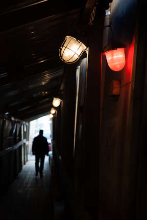 Man walking into the light through a dark tunnel. In the foreground there are two red and white lamps Stok Fotoğraf